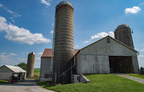 grain wheat metallic silo on cloudy sky background with farm